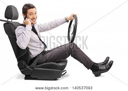 Young man sitting on a vehicle seat and talking on cell phone isolated on white background
