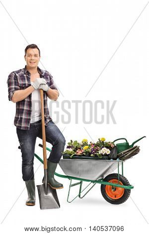 Full length portrait of a cheerful gardener posing with gardening equipment isolated on white background