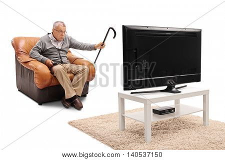 Angry elderly man watching something annoying on TV isolated on white background