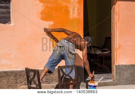 Trinidad, Cuba on December 30, 2015: A man is repainting a wall with a bright orange color. This illustrates the repainting of Cuba in a political sense