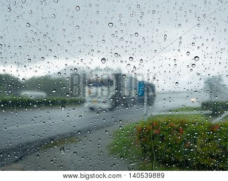 Rain water drop on mirror wall after rainy with blur truck driving on road and fresh green plant on wayside in background. Safety driving on road in rainy concept.