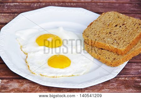 fried eggs sunny side up, with rye dough on a white plate