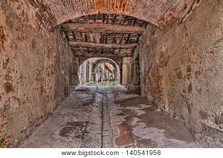 Castiglion Fiorentino, Arezzo, Tuscany, Italy: ancient narrow alley and underpass in the old Italian town