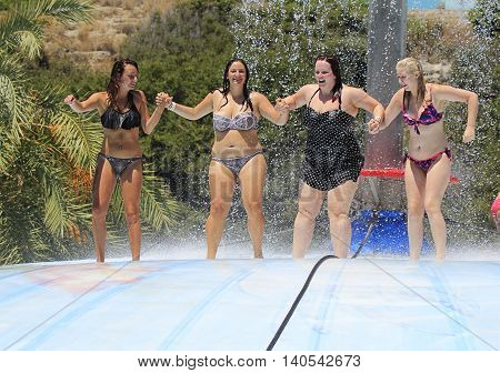 Rhodes Greece-July 52016:Cheerful group of girls jumping on the wet bubble in the water park .Wet bubble is one of many popular game for adults and children in Water park.Water Park is located  on the island of Rhodes in Greece and one of the must popular