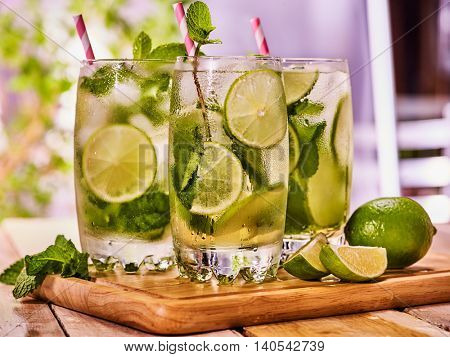 Alcohol drink. On wooden boards small group glasses with alcohol drink and ice cubes. A drink number three hundred one cocktail mohito with knife and mint leaf. Country life. Light background.