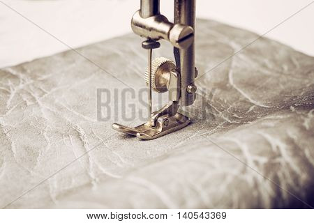 Retro sewing machine needle. Part of work process. Sewing machine leather.