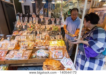 TOKYO JAPAN - 18 JULY 2016 - Seafood snack vendor shows his customer the price in his shop in Tsukiji Fish Market Tokyo Japan on July 18 2016.