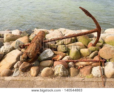 Old Rusty Anchor Forgotten On Stony Coast. Wooden Beam.