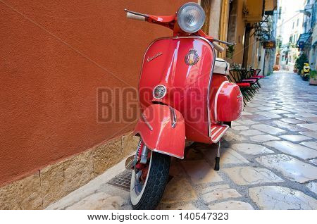 CORFU-AUGUST 22: Vespa scooter on Kerkyra street on August 22 2014 on Corfu island. Greece. Vespa is an Italian brand of scooter manufactured by Piaggio.