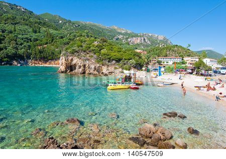 CORFU-AUGUST 26: Famous Palaiokastritsa beach people sunbathe on the beach on August 262014 on Corfu Greece. Palaiokastritsa is a village with famous beaches in the North West of Corfu.