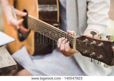 Girl playing Acoustic Guitar Closeup at cafe