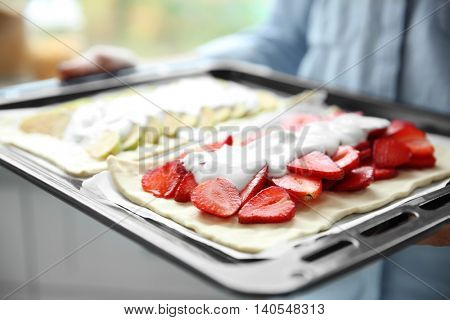 Female hands holding oven tray with strawberry and apple desserts