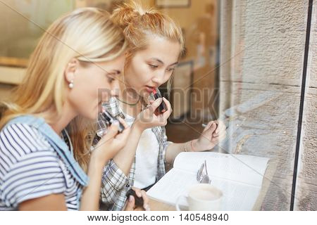 Creative Shot Of Two Blond Girls Rouging Lips Together In A Cosy Café. Two Attractive Female Friends