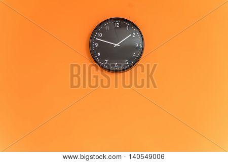 Black clock hanging on a orange blank wall