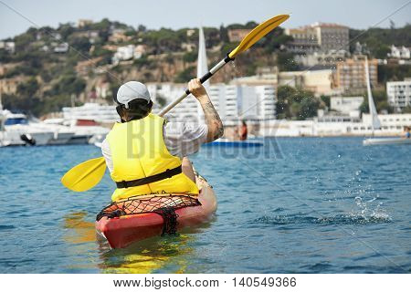 Leisure Activities On The Sea. Back Shot Of Caucasian Man With Tattoo Kayaking And Paddling In Yello
