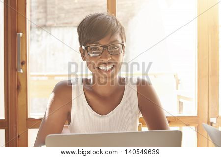 Smiling Spanish Woman In White Tank Top And Spectacles Enjoying Her Studying. Smart Beautiful Female
