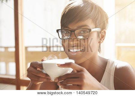 Happy Spanish Woman Enjoying Her Morning Coffee In Sunny Café Near The Window. Attractive And Smilin