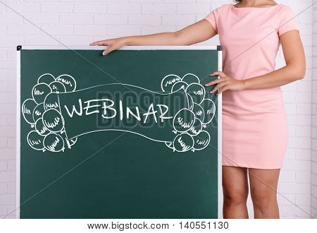 Woman in rosy dress with green blackboard against a brick wall, close up. Webinar concept