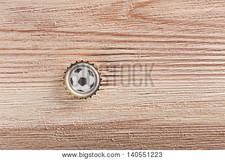 Beer cap with football ball symbol on wooden table