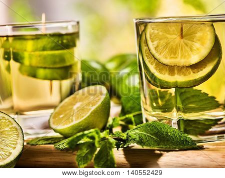 Country drink. On wooden boards are two glasses with green drink and half and slice lime . Drink number three hundred and seven mojito with mint leaf on sunlight . Country life. Light background.