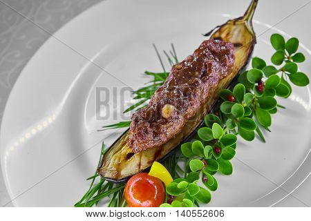 Kebab on grilled eggplant decorated with greens on a white plate