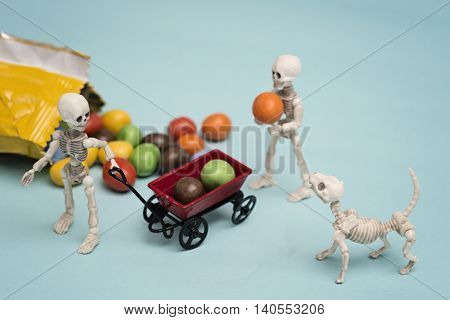 Two skeleton kids getting chocolate candy with toy wagon