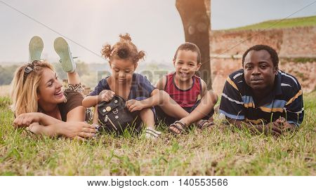 Happy International Family Having Fun And Lying On A Green Grass
