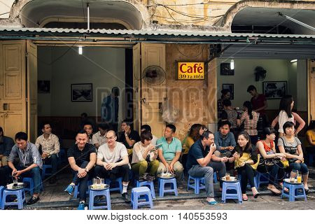 Hanoi, Vietnam - March 18, 2015 - Young people drink coffee in side walk