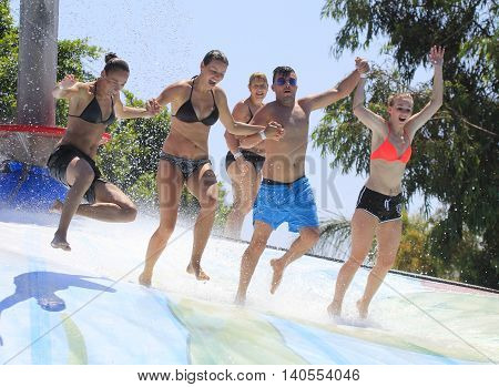 Rhodes Greece-July 15 2016:Cheerful group of young people jumping on the wet bubble in the water park .Wet bubble is one of many popular game for adults and children in Water park..Water Park is located on the island of Rhodes in Greece