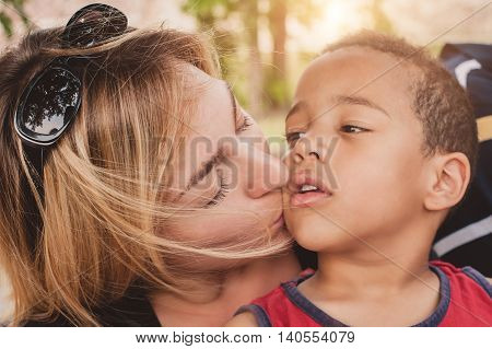 Happy mother kissing her little son. International family