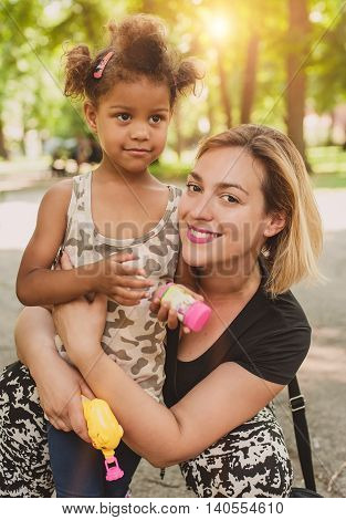 Mother and daughter having fun and enjoying in the park. International family