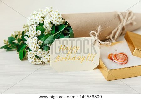 Birthday Card with Golden Present Box with Glass Heart. Bouquet White Small Flowers in Brown Craft Paper with String.White Wooden Texture Background.Selective Focus