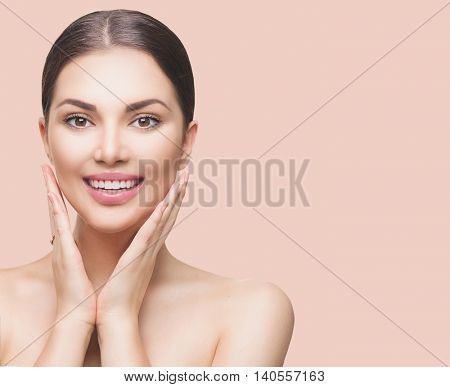 Beauty Spa Woman with perfect skin Portrait. Beautiful Brunette Girl touching her face and smiling, pampering her skin. Beige background