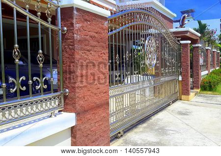 ornate scrolled metal arched gate in block and brick wall combo with metal fence, in front of a two-story house, cars glimpsed behind the fence, Songkhla, Thailand