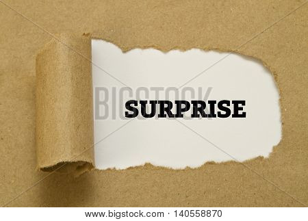 SURPRISE word written under torn paper .