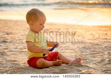 Boy sitting on beach and playing with spade at sunset