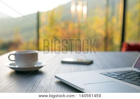 Computer Coffee Mug and Telephone on black wood table green flora beyond large windows on background. Focus on front part of laptop and touchpad