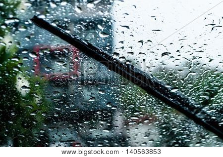 raindrops and wiper on car windshield. use wipers and drive slowly in the rain for safety.