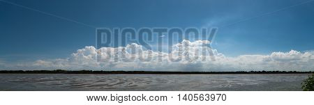 Panoramic view of white fluffy cloud against clear blue sky over the horizon with muddy wet land on the ground.