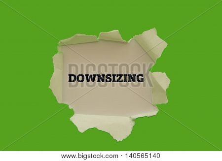 DOWNSIZING word written under torn paper .