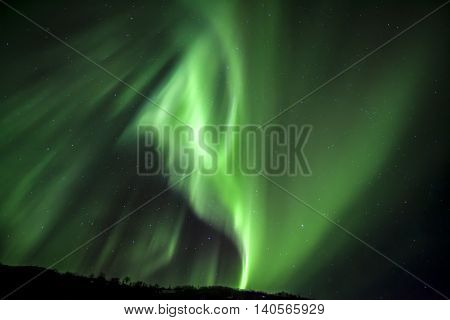 Strong bright green aurora northern lights over mountain Tromso Norway