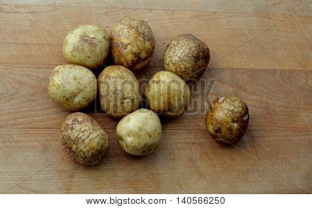 New Baby White Potatoes: Grouped together on a wooden cutting board.