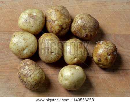 Group of new baby white potatoes on wooden cutting board.
