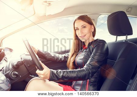 Young beautiful woman steering wheel driving a car. Confident smiling lady in red dress driving a car