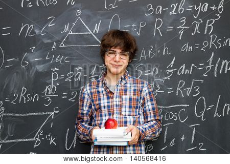 Boy in glasses holding books with apple, blackboard filled with math formulas background