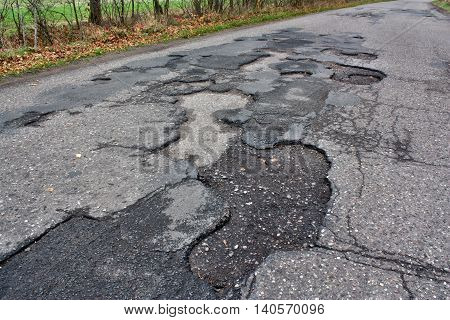 Dangerous road with holes destroyed way asphalt