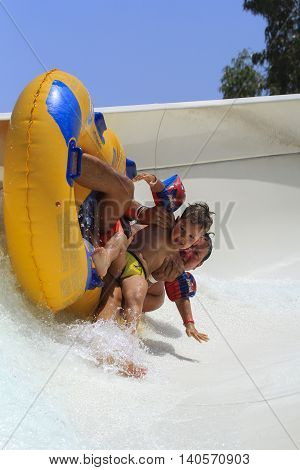 Rhodes Greece-July 26 2016:father and sun drive with tube on the rafting slide in the Water park.Rafting slide is one of many popular game for adults and children in park.Water Water Park is located on the island of Rhodes in Greece