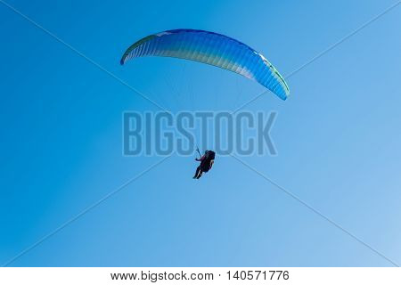 Paragliding in the sky. Man flying a paraglider on the sun.