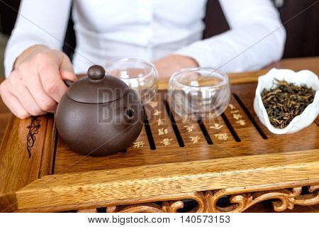Young woman conducting tea ceremony with chinese tea set