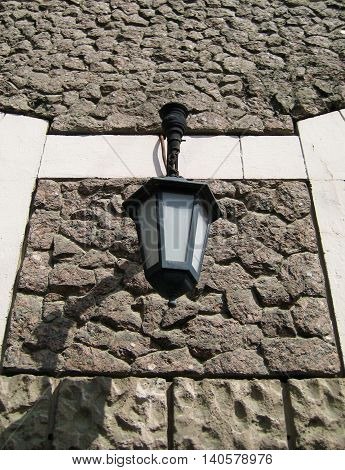 Classic black and white street lantern hanging outside at the house on a brick wall background